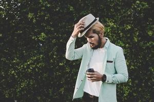 glücklicher Hipster-Mann, der heißen Kaffee hält foto