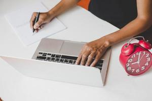 Geschäftsfrau sitzt am Schreibtisch und arbeitet am Computer foto