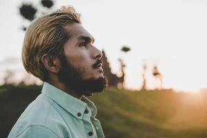 junger Hipster-Mann, der in einem Park steht foto