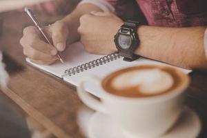 eine Kaffeetasse auf einer Holzbar neben einem Hipster in einem Café