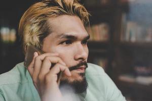 Geschäftsmann-Hipster, der auf Smartphone an der Café-Bar spricht