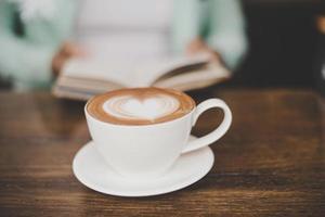 verschwommener Mann, der in einem Café liest und Kaffee trinkt foto