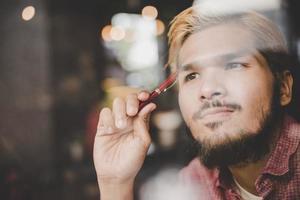 nachdenklicher junger Hipster-Mann, der in einem Coffeeshop-Denken sitzt foto