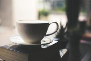 Vintage Farbton Tasse Kaffee mit Buch in einem Café foto
