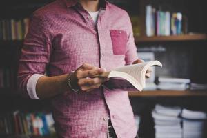 junger Hipster-Mann, der Buch in einer Bibliothek liest