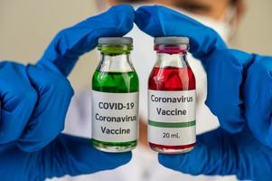 Ein Wissenschaftler, der Maske und Handschuhe trägt, trägt Fläschchen mit Impfstoffen zum Schutz vor Covid-19 foto