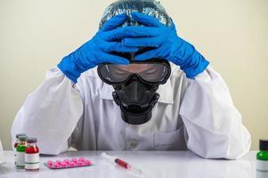 Wissenschaftler am Tisch mit Impfstoffen und Drogen foto
