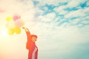 junge schöne Frau, die bunte Luftballons im hellen Himmel genießt foto