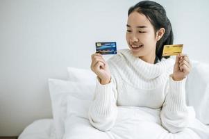 junge Frau mit einer Kreditkarte, die auf Bett lächelt foto