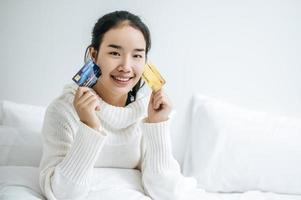junge Frau mit einer Kreditkarte, die auf Bett lächelt