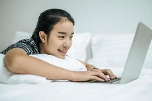 eine Frau in einem gestreiften Hemd spielt auf ihrem Laptop auf ihrem Bett