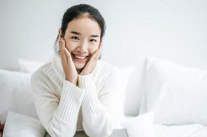 junge Frau sitzt auf ihrem Bett mit Händen, die Wangen berühren