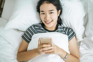 junge Frau mit ihrem Smartphone auf dem Bett