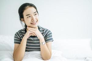 Eine Frau sitzt mit den Händen unter dem Kinn und lächelt