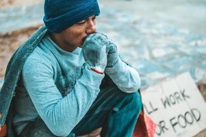 Ein Mann sitzt und bettelt mit Obdachlosen. Bitte helfen Sie foto