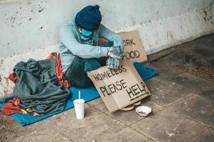 Mann sitzt neben der Straße und trägt eine medizinische Maske mit einer obdachlosen Nachricht foto