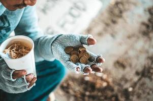 Bettler unter der Brücke mit einer Tasse mit Münzen und Instantnudeln