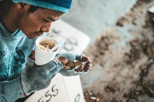 Bettler unter der Brücke mit einer Tasse mit Münzen und Instantnudeln foto