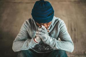 Bettler sitzt unter der Überführung mit einem Bitte helfen Sie Zeichen foto