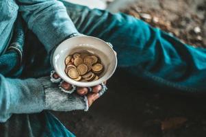 Bettler sitzt unter einer Brücke mit einer Tasse Geld
