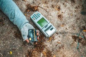 Bettler schläft auf der Straße mit Kreditkartenautomat foto
