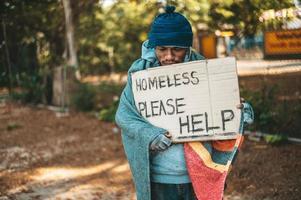 Bettler steht mit obdachlosen Nachrichten auf der Straße, bitte helfen Sie foto