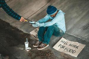 Bettler sitzen unter der Brücke mit einem Kreditkarten-Swipe-Automaten foto