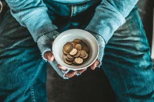 Bettler sitzt unter einer Brücke mit einer Tasse Geld foto