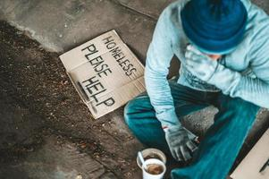 Bettler unter der Brücke mit einer Tasse Instantnudeln und einem Hilfeschild