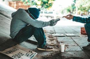 Bettler sitzen unter der Überführung mit einem Kreditkarten-Swipe-Automaten foto