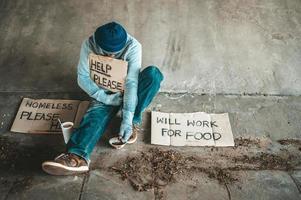 Bettler unter der Brücke mit einer Tasse Instantnudeln und einem Hilfeschild foto