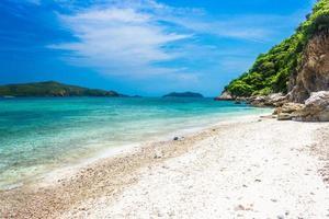 tropischer Inselfelsen am Strand mit klarem blaugrünem Wasser foto