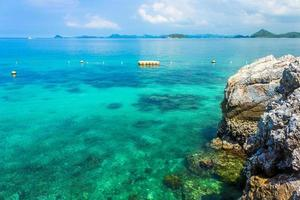 tropische Inselfelsen am Strand durch Wasser mit bewölktem blauem Himmel foto