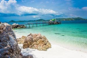 Felsen und hölzerner Pier am Strand mit Wasser und bewölktem blauem Himmel