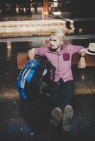 junger Hipster-Mann, der auf hölzerner Bank am Bahnhof sitzt foto