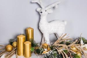 Weihnachtsschmuck aus weißem Hirschspielzeug und goldenen Kerzen foto