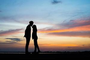 Silhouette des jungen Paares zusammen während des Sonnenuntergangs