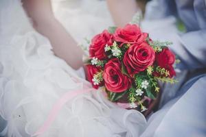 Braut hält einen roten Rosenstrauß der Hochzeit in den Händen foto