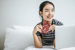 junge Frau sitzt auf ihrem Bett und hält einen Wecker