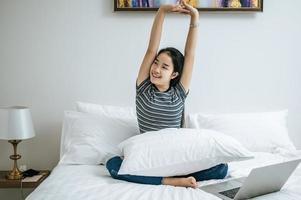 junge Frau sitzt auf ihrem Bett und streckt die Arme aus