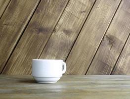 weißer Becher gegen Holz foto