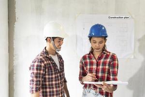 junge asiatische Ingenieure mit Schutzhelmen foto