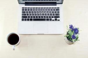 Laptop und Kaffee auf einem Schreibtisch foto