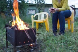 Person, die in der Nähe des Lagerfeuers sitzt foto