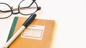 Notizbuch mit Stift und Brille foto