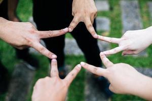 Freunde machen zusammen Sternform aus Fingern