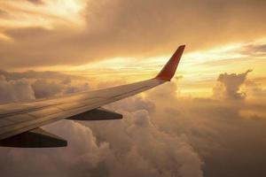 Flugzeugflügel und Wolken bei Sonnenuntergang