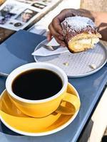 Nahaufnahme der Person, die ein Sauerteigkuchenbrötchen und schwarzen Kaffee genießt foto