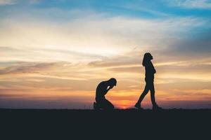 Silhouette des Paares, das auf der Straße bei Sonnenuntergang aufbricht