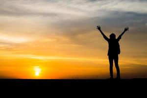 Wanderer mit einem Rucksack entspannen und Sonnenuntergang genießen foto